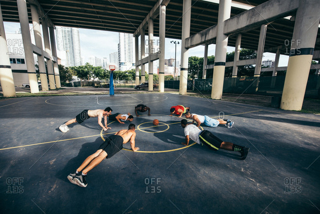 Friends on basketball court in a circle doing push ups