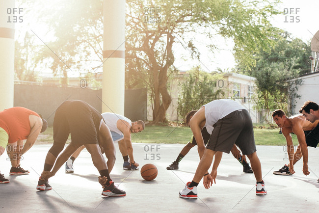 Friends on basketball court in a circle bending forwards warming up