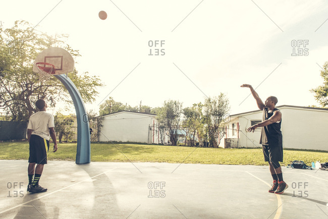 Men on basketball court scoring basketball hoops