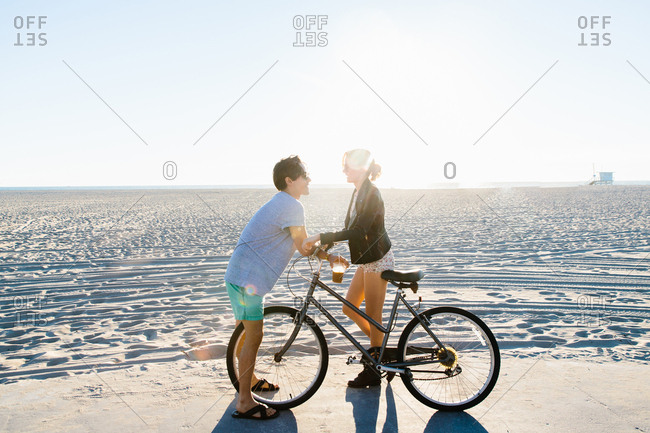 Young couple with bicycle chatting on sunlit beach, Venice Beach, California, USA