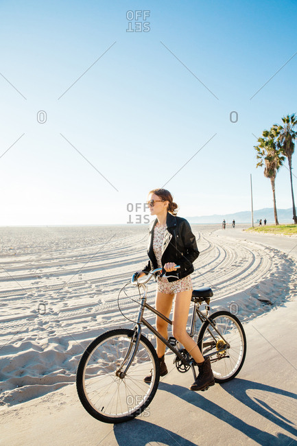 Young woman on bicycle gazing from beach, Venice Beach, California, USA
