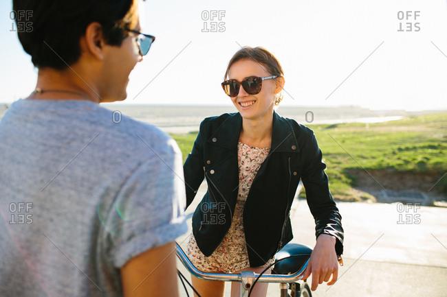 Young couple chatting on beach, Venice Beach, California, USA
