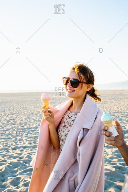 Stylish young woman with boyfriend eating ice cream cone strolling on beach, Venice Beach, California, USA
