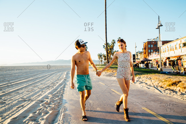 Young couple wearing swimming costume and shorts strolling at beach, Venice Beach, California, USA
