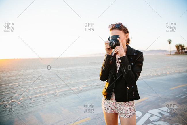 Young woman photographing with instant camera on beach, Venice Beach, California, USA