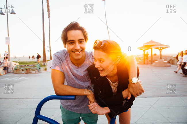 Portrait of happy young couple leaning against bicycle sculpture at coast, Venice Beach, California, USA