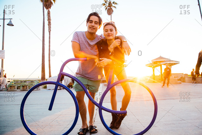 Portrait of young couple leaning against bicycle sculpture at coast, Venice Beach, California, USA