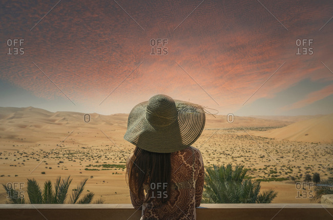 Woman on balcony, looking at desert view, at sunset, rear view, Abu Dhabi, Abu Dhabi Emirate, UAE