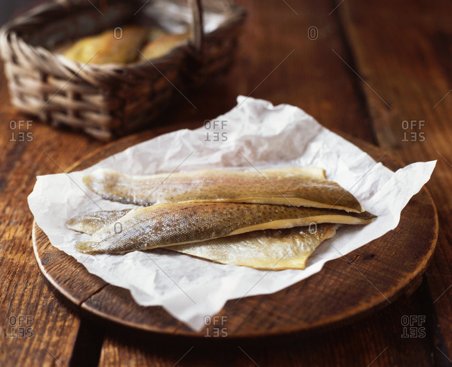 Sea bass fillets on wooden chopping board