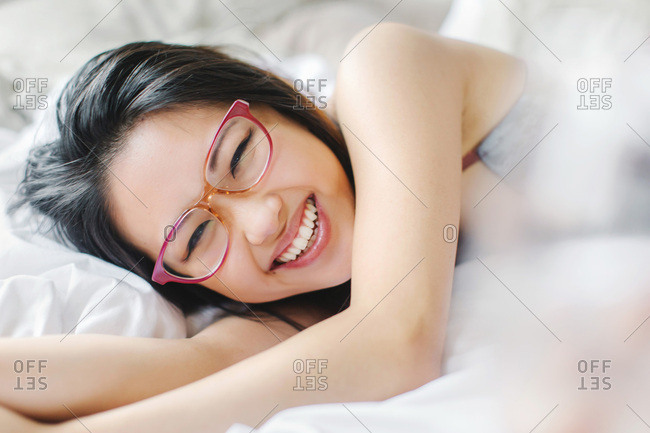 Young woman, wearing spectacles, lying on bed, laughing