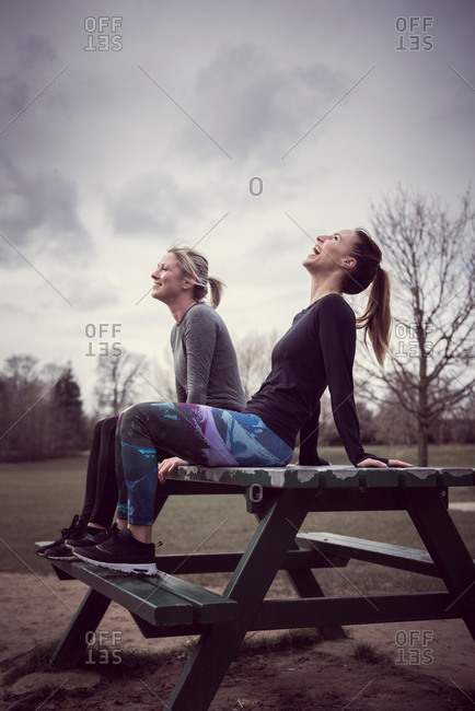 Women wearing sports clothing sitting on picnic table, head back laughing