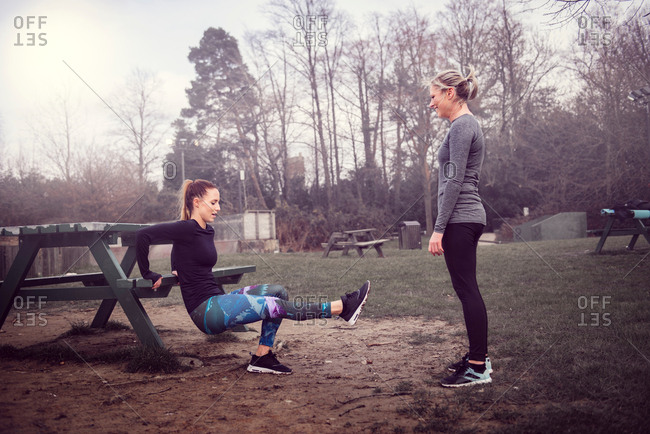 Women doing reverse push up on picnic bench
