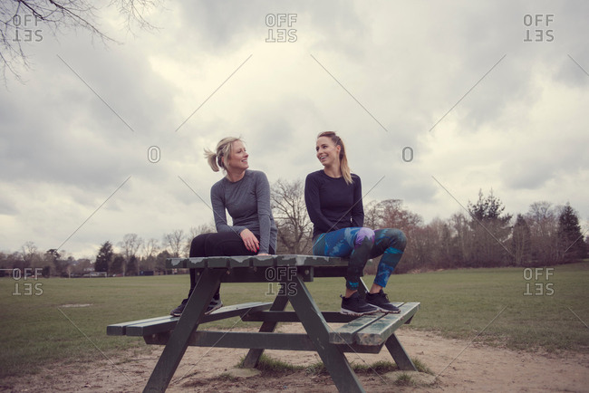 Women wearing sports clothing sitting on picnic table chatting