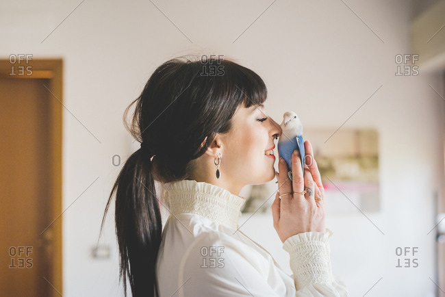 Young woman holding pet bird indoors