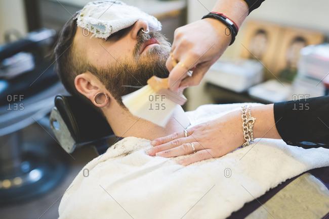 Female barber tidying man's beard in shop