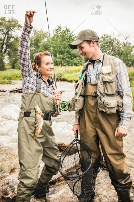 Man and woman standing in river wearing waders holding fishing rod smiling