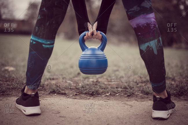 Rear view of womans low section, open legged holding kettle bell