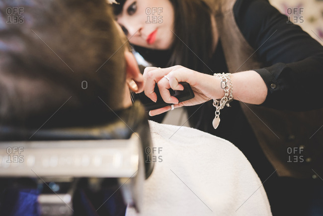 Female barber trimming man's beard in shop