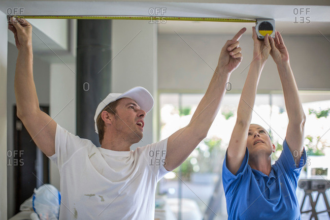 Couple, arms raised, using tape measure to measure ceiling