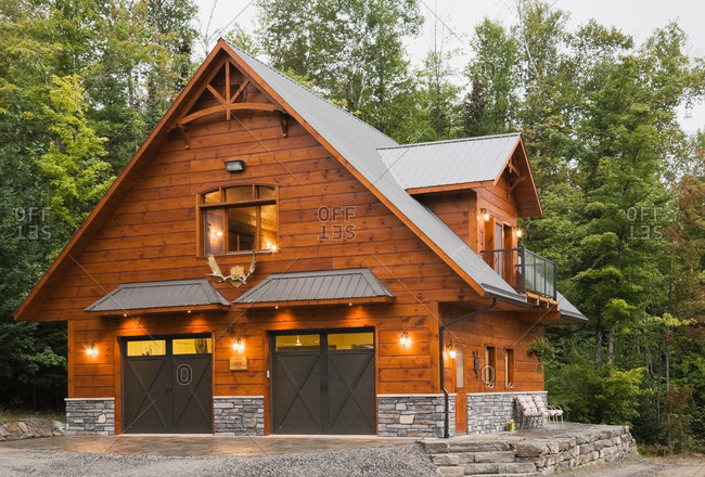 Exterior of cottage style Eastern white pine log house with double garage