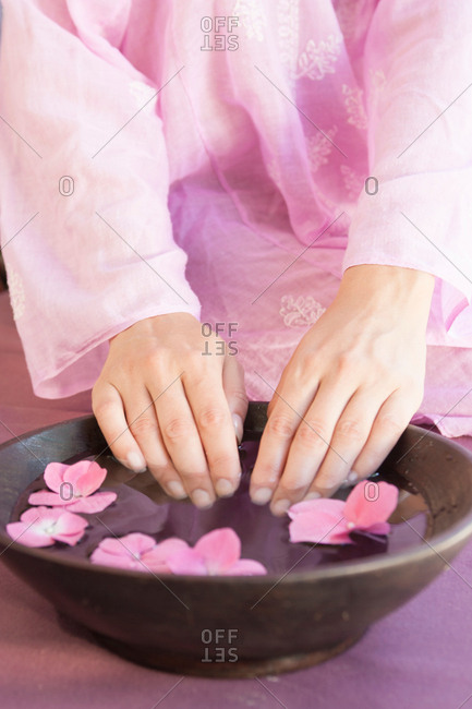 Cropped shot of young woman's fingernails soaking in bowl of flower petal water at spa
