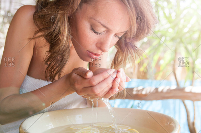 Young woman with cupped hands cleansing face over bowl at spa
