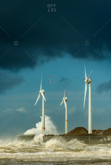 Three wind turbines amidst fierce storm waves at coast, Boulogne-Sur-Mer, Nord-Pas-de-Calais, France