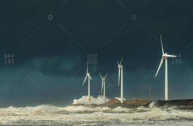 Four wind turbines amidst fierce storm waves and clouds at coast, Boulogne-Sur-Mer, Nord-Pas-de-Calais, France