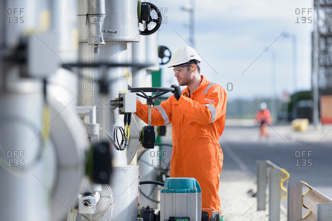 Worker turning valve at gas-fired power station