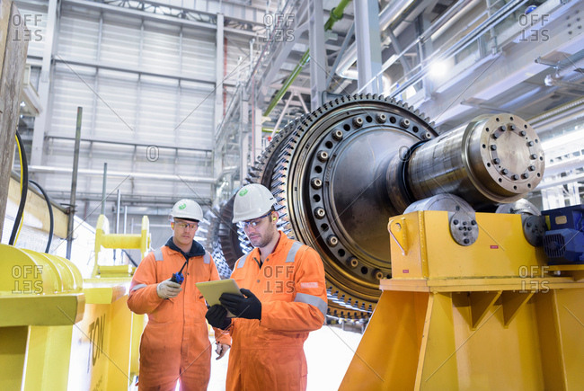 Workers with gas turbine in gas-fired power station