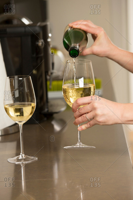 Hands of woman pouring glasses of white wine at kitchen counter