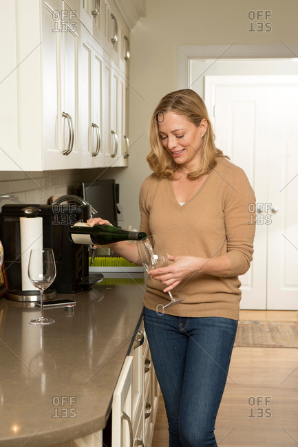 Woman pouring white wine into glass in kitchen