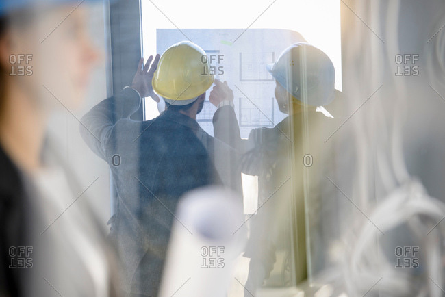 Blurred image of architect and businesswoman looking at blueprint in new office