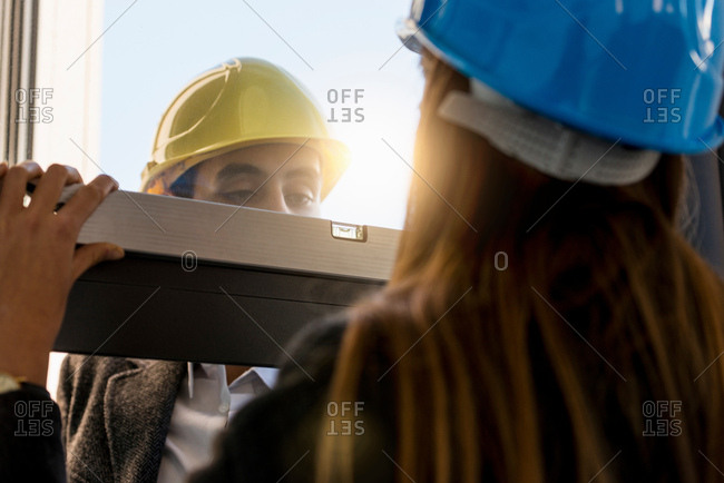 Architect and businesswoman wearing hard hats  inspecting new office window