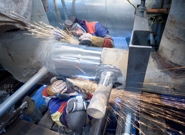 Workers grinding pipe in gas-fired power station