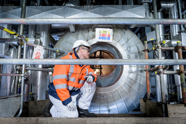 Worker looking into condenser in gas-fired power station