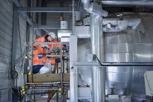 Workers inspecting condenser in gas-fired power station