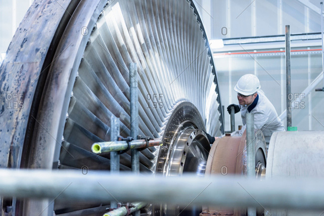 Engineer inspecting steam turbine in gas-fired power station