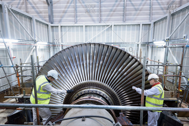 Engineers inspecting steam turbine in gas-fired power station