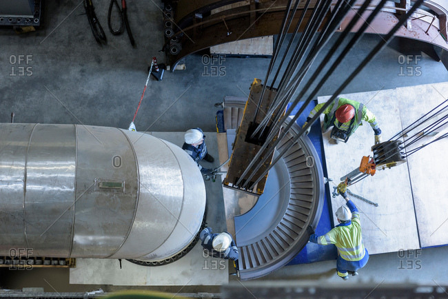 Engineers crane steam turbine parts during outage in gas-fired power station