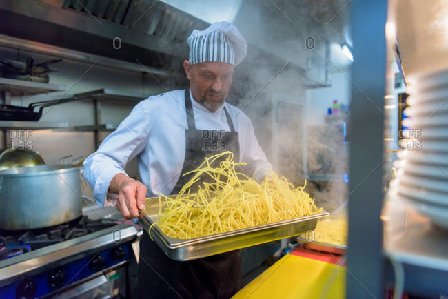 Chef preparing freshly made pasta in traditional Italian restaurant kitchen