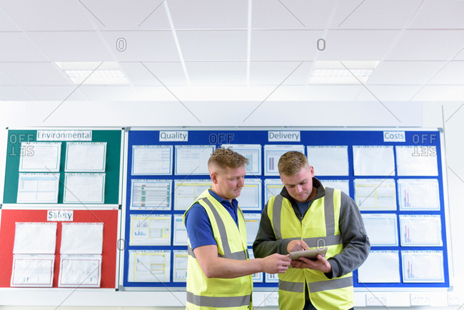 Engineers with digital tablet in front of productivity and safety board in engineering factory