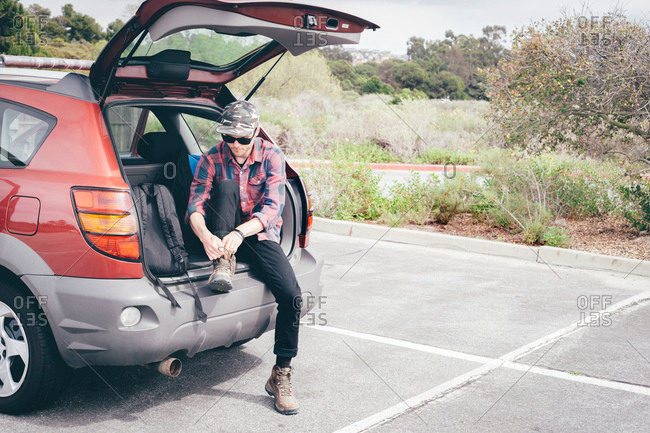 Male hiker sitting on car boot tying hiking boot laces, Crystal Cove State Park, Laguna Beach, California, USA