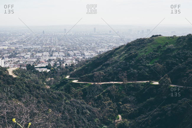 Elevated view of hills and winding road with distant smoggy cityscape, Los Angeles, California, USA