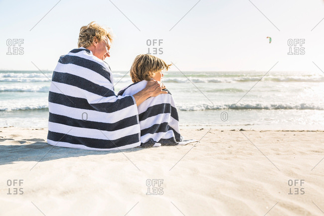 Rear view of father and son sitting on beach wrapped in blanket
