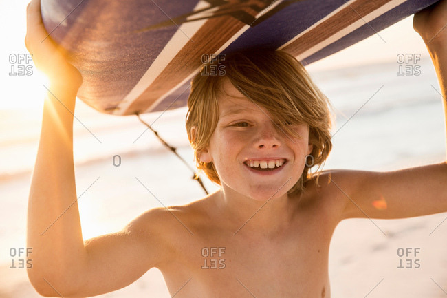 Boy carrying surfboard over head smiling