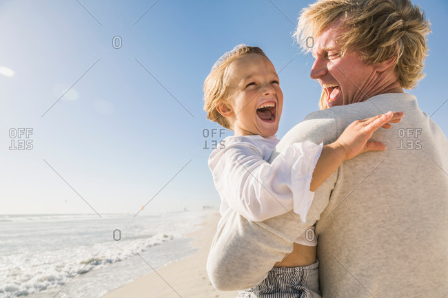 Father on beach carrying son, mouth open smiling