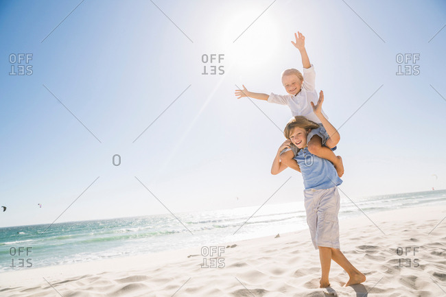 Full length view of big brother on beach carrying brother on shoulders, arms raised smiling