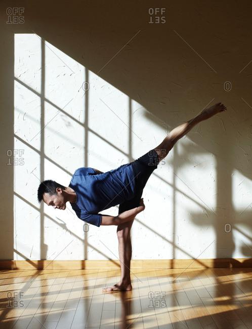 Man doing yoga in studio, in half moon bind position