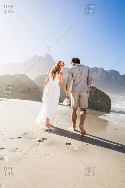 Full length rear view of couple walking on beach holding hands